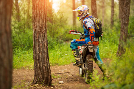 Motocross driver in the forest. motorcycle driver looks, concept, active lifestyle Stok Fotoğraf
