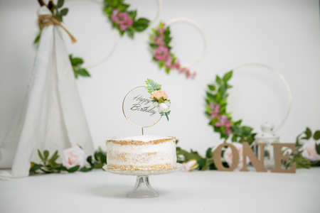 Festive background decoration for birthday celebration with gourmet cake, letters saying one in studio, cake smash first year concept