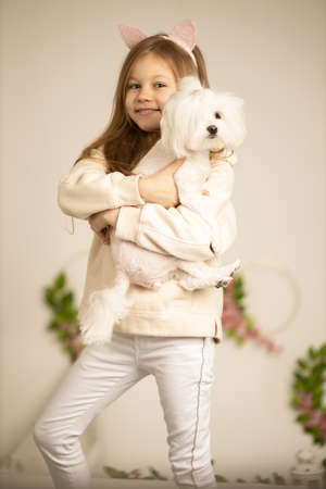 Beautiful lovely cheerful girl holding her pet lapdog over beige bakground
