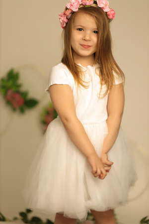 Smiling baby girl 3-4 year old on a beige background. Wearing floral wreath. Looking at camera. Childhood. Elegance Reklamní fotografie