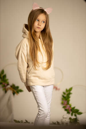 pensive girl 8-9 years old in a beige sweatshirt and white pants, holding her hands behind a bed on a cream background