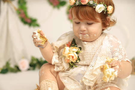 cute red haired baby girl smashes her first birthday cake