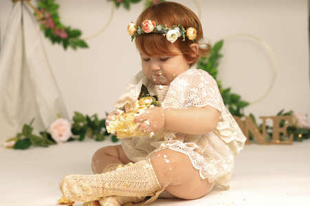 little girl smashes a cake on his first birthday. Smash cake, stylized photo session for a childrens party