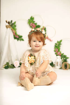 Little 1 years old red hair beautiful tender smiling girl, childhood celebration concept. Spring concept. Child in flowers. Studio photoshoot. Indoors