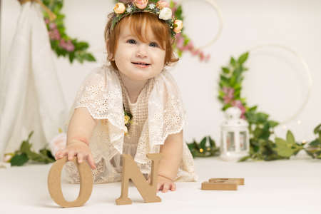 Little cute redhead girl in a beautiful white dress in a spring light studio decorated with flowers