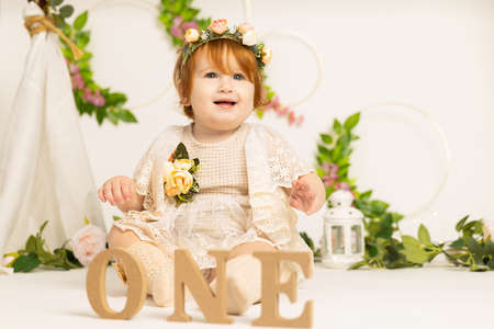 One year old baby girl celebrates birthday in letters ONE on white background with flowers