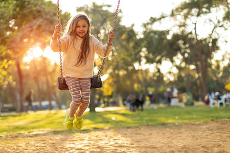 Girl holding chains of swings and swinging on a bright sunny day