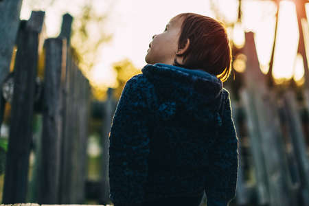 little girl sits on a wooden slide with her back and looks at the sky Reklamní fotografie