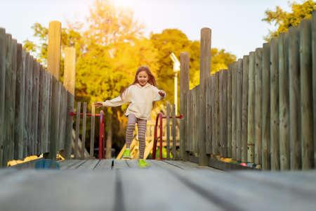 blonde child girl running on wooden bridge with sunlight