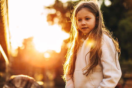 Little Caucasian blonde girl in the park, in the rays of the setting sun Reklamní fotografie