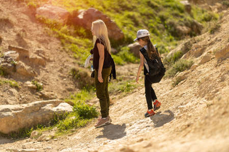 mom and daughter walking in the mountains