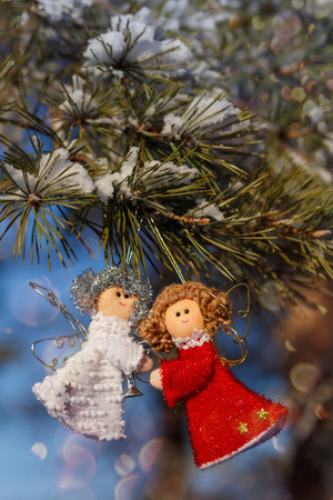 sprig: Two small dolls angels with sprig of pine sprinkled with snow. Stock Photo