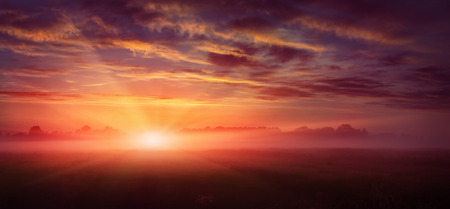 fantastic landscape. majestic misty morning over meadow. colorful sky with overcast clouds, under the influence of sunlight. dramatic picturesque scene. beauty of the world. creative images Stock Photo