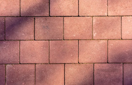 Pavement of rectangular colored stones in bright light with shadow