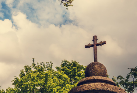 cast metal cross. element headstone carved from sand stone. old sculpture covered with moss. on sky background. soft selective fokus. vintage style. toning effect Archivio Fotografico