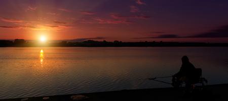 素晴らしい風景、湖の上の多色の空。雄大な日の出。日没時の釣りフィーダー。夕暮れ時の漁師のシルエット。背景として使用します。多くのカラ