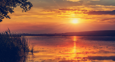 majectic sunset over the lake. overcast clouds in the sky , gloving in sunlight. picturesque dramatic scene. beauty in the world. 写真素材