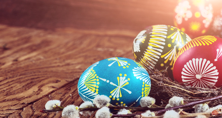 Easter background. colored Easter eggs in the nest and composition of dried flowers and plants. on wooden background. easter theme. happy easter.