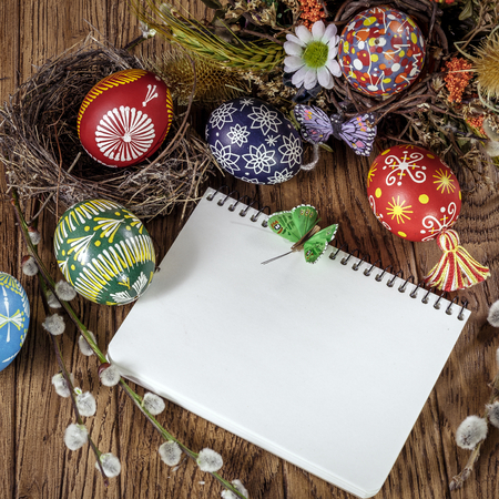 Easter theme. Easter greeting card colored Easter eggs and blooming willow over wooden background with copy space. Happy Easter