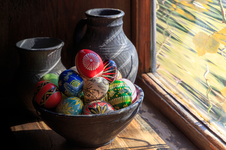 Easter eggs in a clay plate. lit by the sun from the window. wooden texture. Easter background. happy Easter. Stock Photo