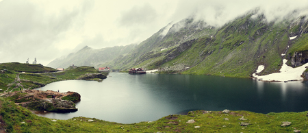 nature landscape. Balea Lake, Fagaras Mountains, Romania in the autumn. with overcast clouds inthe sky. creative artistic image. retro style.  toning effect.