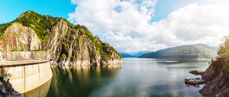 summer scenery. of Vidraru Lake and Dam glowing  in sunlight. creative image. location. Vidraru Dam, Romania. Carpathian Mountains, Fagaras ridge. Stock Photo