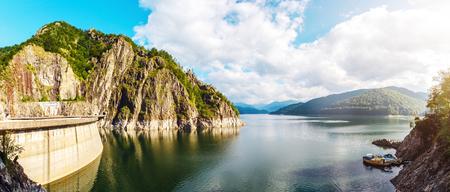 summer scenery. of Vidraru Lake and Dam glowing  in sunlight. creative image. location. Vidraru Dam, Romania. Carpathian Mountains, Fagaras ridge. Stok Fotoğraf