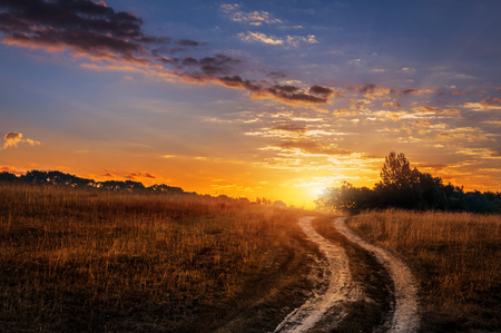 landscape with rut road on sunset sky. with sunbeam background. unusual amazing sunset. creative image
