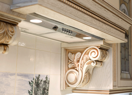 extractor fan in the kitchen is decorated with carvings element. furniture in classic style. white tree with gold trim. patina. carving. small depth of field. luxury furniture 免版税图像