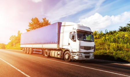 big white truck on the road in a rural landscape at sunlight. perfect sky. over the asphalt road at sunset. logistics transportation and cargo freight transport industrial business commercial concept