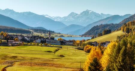 Breathtaking Sunny landscape in Autumn. Wonderful Alps Highland under sulight. Beautiful view of the lake Muta Haidersee and Ortler peak, located near the village St. Valentin, Alps, Italy, Europe. Standard-Bild