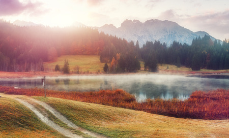 Womderful Autumn landscape. Road on meadow with grass on top view. Fairy Alpine lake Geroldsee with morning fog under sunlit. Dramatic Impressive scene. Amazing nature background.