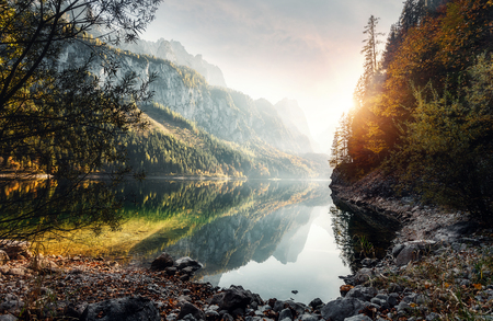 Awesome alpine highland at sunset with colorful sky. Scenic image of fairy-tale lake surrounded by Rocky Mountains in sunlit. Amazing Alps valley. Incredible autumn Landscape. Picturesque background