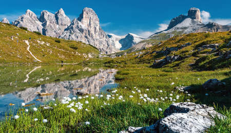 Awesome Alpine highlands in sunny day. Amazing Summer Landscape of Dolomites Alps. Wonderful Panoramic view at Mountains Range and calm lake on foreground of Tre Cime di Lavaredo National park. Standard-Bild