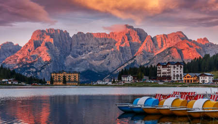 Misurina Lake with colorful sky during sunrise. Wonderful Nature landscape. View on lake with boats and Majestic mountains peak in clouds, on background. Famous World place. Creative image