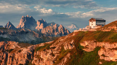 Wonderful Sunny Landscape of Dolomite Alps during sunrise. Panoramic view of famous Dolomites mountain peaks glowing in beautiful golden evening light at sunset in summer, South Tyrol, Italy