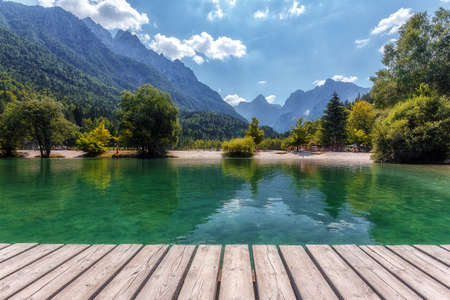 Awesome alpine highlands in summer. Lake with Wooden Pier and mountain peaks on background, in sunny day. Beautyful Nature Scene. Jasna lake in Julian Alps, Kranjska gora, Slovenia.