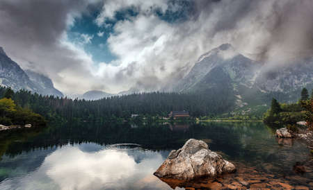 A view of a Popradske Pleso in Slovakian part of Tatra mountains, Slovakia. Majestic rocky peaks in clouds, reflected in turquoise water. Wonderful Picturesque scenery Standard-Bild