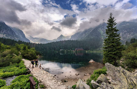 Beautiful alpine lake in morning. Overcast summer day in the Slovak High Tatra mountains - Popradske Pleso mountain lake and surrounding peaks - popular travel and hiking destination in Central Europe.