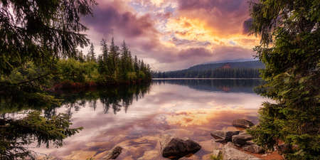 Colorful Autumn landscape under warm Sunlit. Majestic mountain lake in National Park High Tatra at sunset. Dramatic unusual scene. Picturesque Sky glowing by sunlight. Strbske pleso, Slovakia, Europe. Standard-Bild
