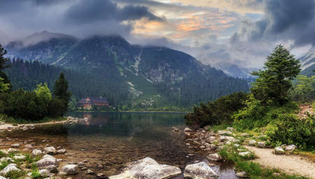 Beautiful alpine lake in morning. Overcast summer day in the Slovak High Tatra mountains - Popradske Pleso mountain lake and surrounding peaks - popular travel and hiking destination in Central Europe