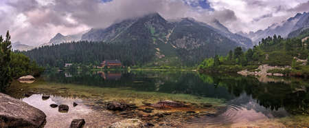 Amazing Landscape. Alpine lake with colorful overcast sky and mountains. Incredible view of beautiful mountains in High Tatras. Magic Lake Popradske pleso, Slovakia. impressively Wild nature Standard-Bild