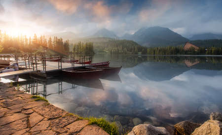 A wonderful Colorful Sunset at lake Strbske pleso, in High Tatra. Picturesque Dramatic sky glowing in sunlight, over the Fairytale calm lake. Scenic image of woodland in sunlit. Autumn Landscape. Standard-Bild