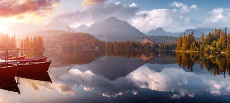 Incredible Nature Landscape. Beautiful view of traditional wooden boats on Strbske Pleso Lake during sunset. Awesome Sunny natural scene. Popular travel and hiking destination. Beautiful on the World.