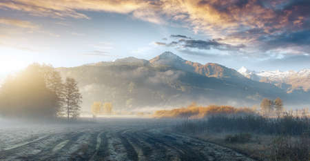 Wonderful dramatic scene. fantastic foggy sunrise over the meadow with colorful clouds. Mountains during sunset. Beautiful natural landscape in the summer time. Foggy Landscape. Early Morning Mist Standard-Bild