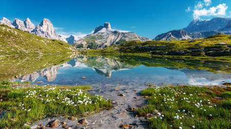 Amazing Nature Landscape. Alpine lake with crystal clear water and frash grass and flowers. Perfect Blue sky and mountains peaks. Incredible view of Dolomites Alps. Tre Cime di Lavaredo National park Standard-Bild