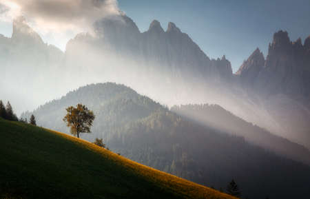 Awesome Alpine highlands during sunrise. foggy morning in Dolomites mountains - mountain range silhouttes. Amazing Nature landscape. fog and cloud mountain valley scenery. Majestic sunset