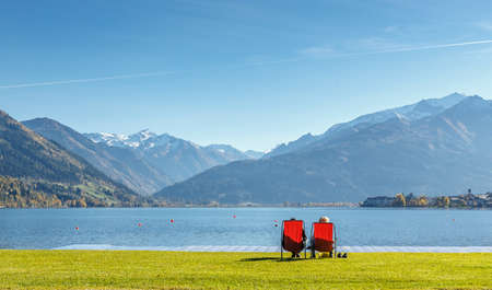 Stunning Nature Landscape. Romantic couple, near a lake sitting on chairs. Panoramic view of beautiful mountain landscape in Alps with Zeller Lake in Zell am See, Salzburger Land, Austria