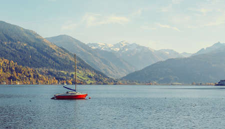 Panoramic view of beautiful mountain landscape in Alps with Zeller Lake in Zell am See, Salzburger Land, Austria. Red yaht at calm water Wonderful Lake. under bright sunlight. Standard-Bild