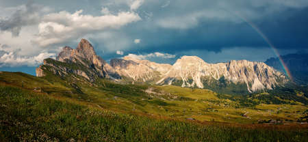 The rainbow over the seceda ridge, idyllic mountain scenery in the Dolomites Alps with Majestic Peaks, Overcast sky and Rainbow. Odle mountain range, Val Gardena in Dolomites. Italy. Amazing Nature